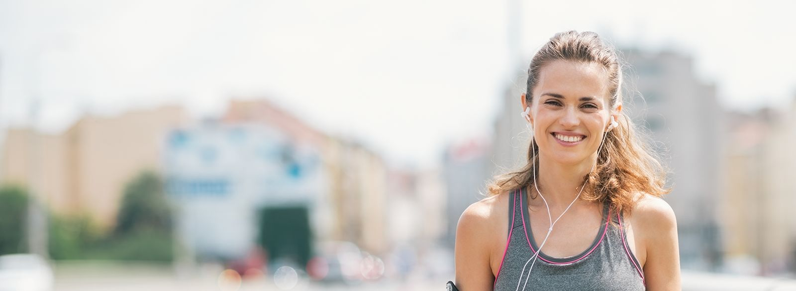 woman with a beautiful smile jogging in the city