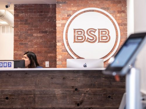 an BSB employee behind the front desk and a BSB logo on the wall behind that